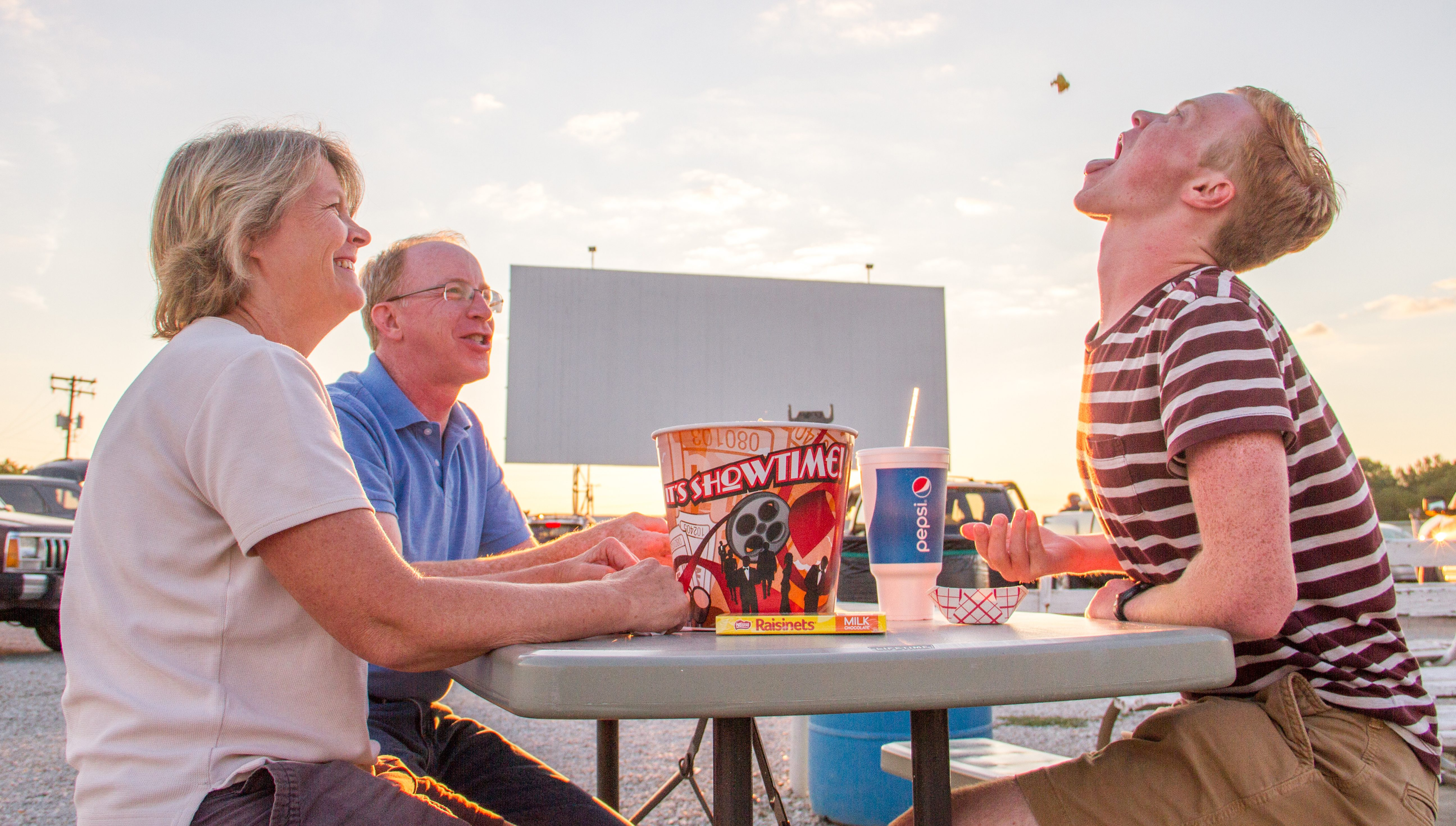 Family eating popcorn outside the drive-in.