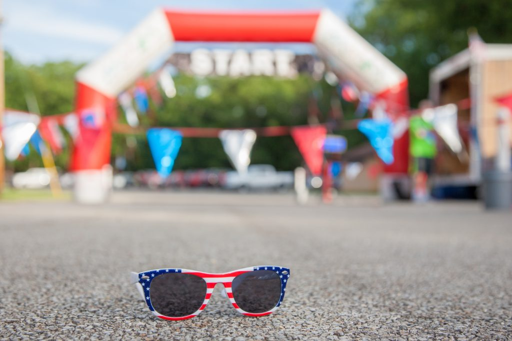 Patriotic sunglasses sitting on the pavement.