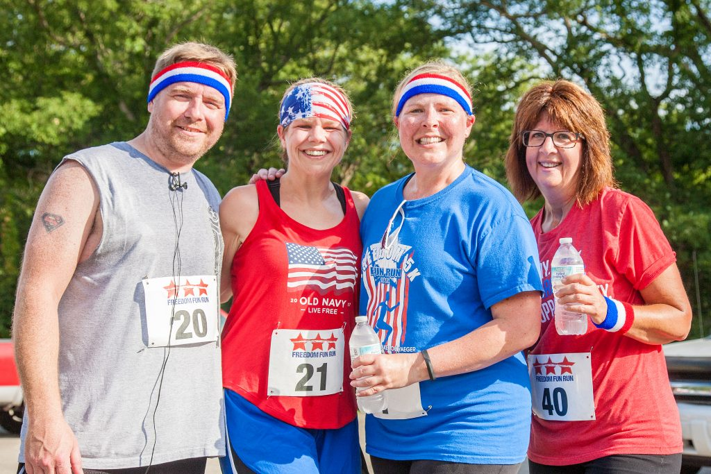 Four runners in red, white, and blue at the patriotic Freedom Fun Run.