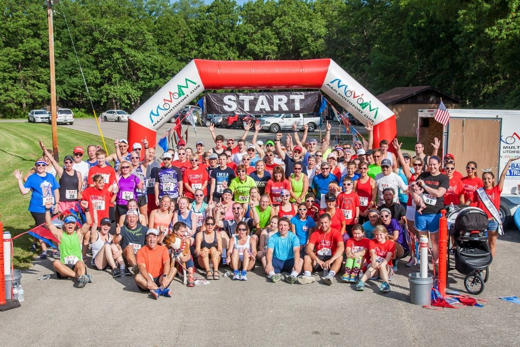 Group photograph of 100 runners at the finish line at the Freedom Fun Run.