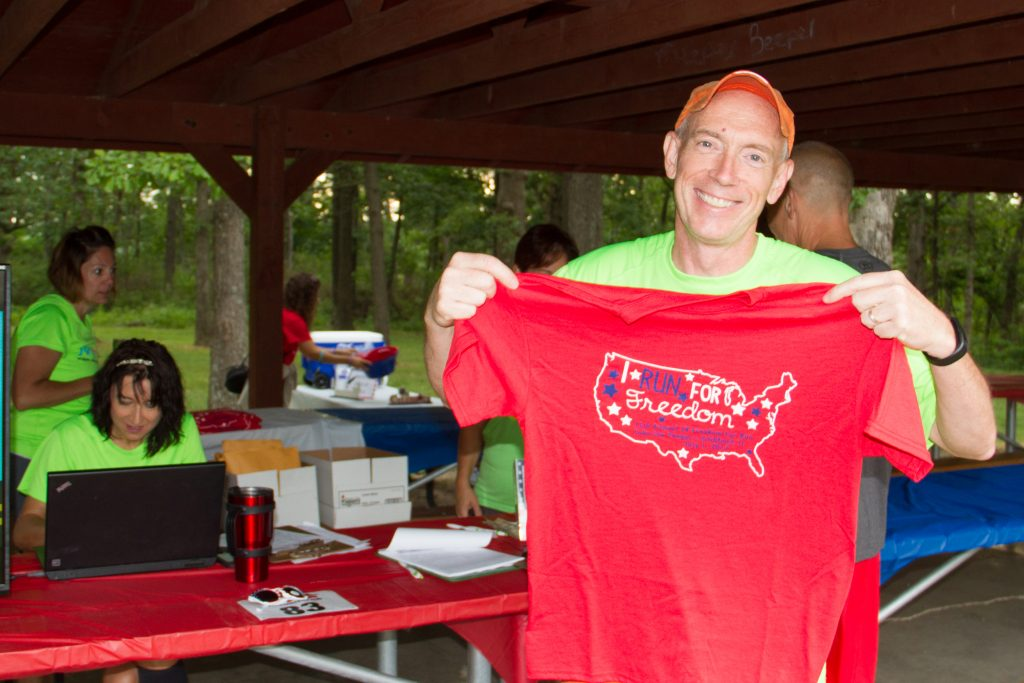 Displaying a t-shirt at the Freedom Fun Run registration.