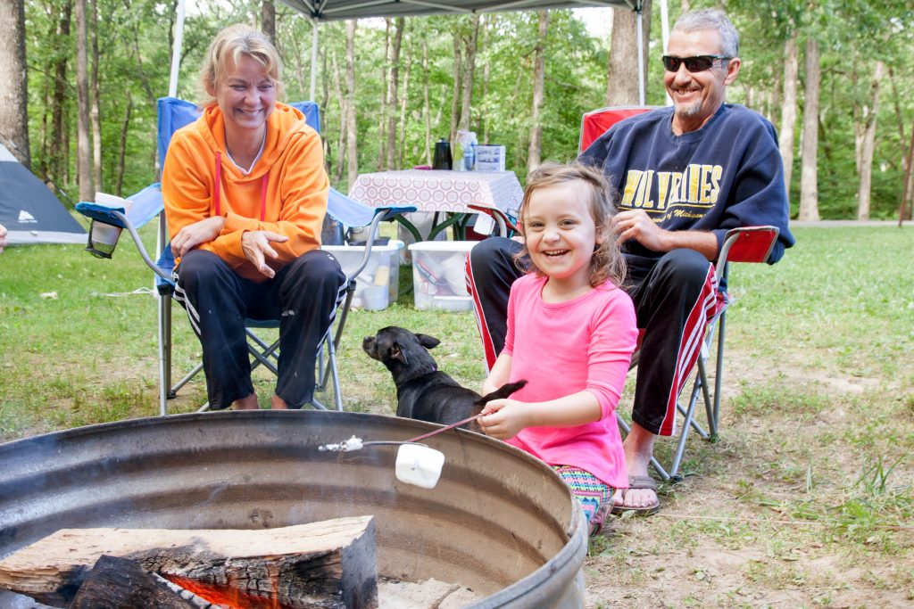 Family and dog around a campfire ring at the primitive campground.