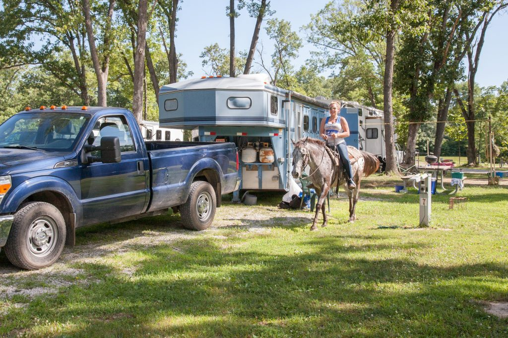 An equestrian campground site with a woman on a horse.