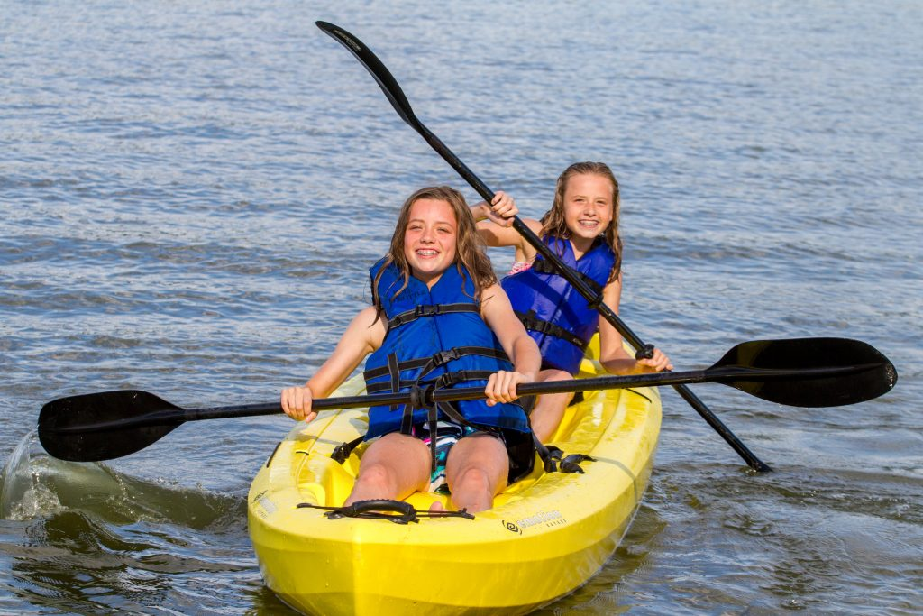 Two girls paddle a yellow kayak.