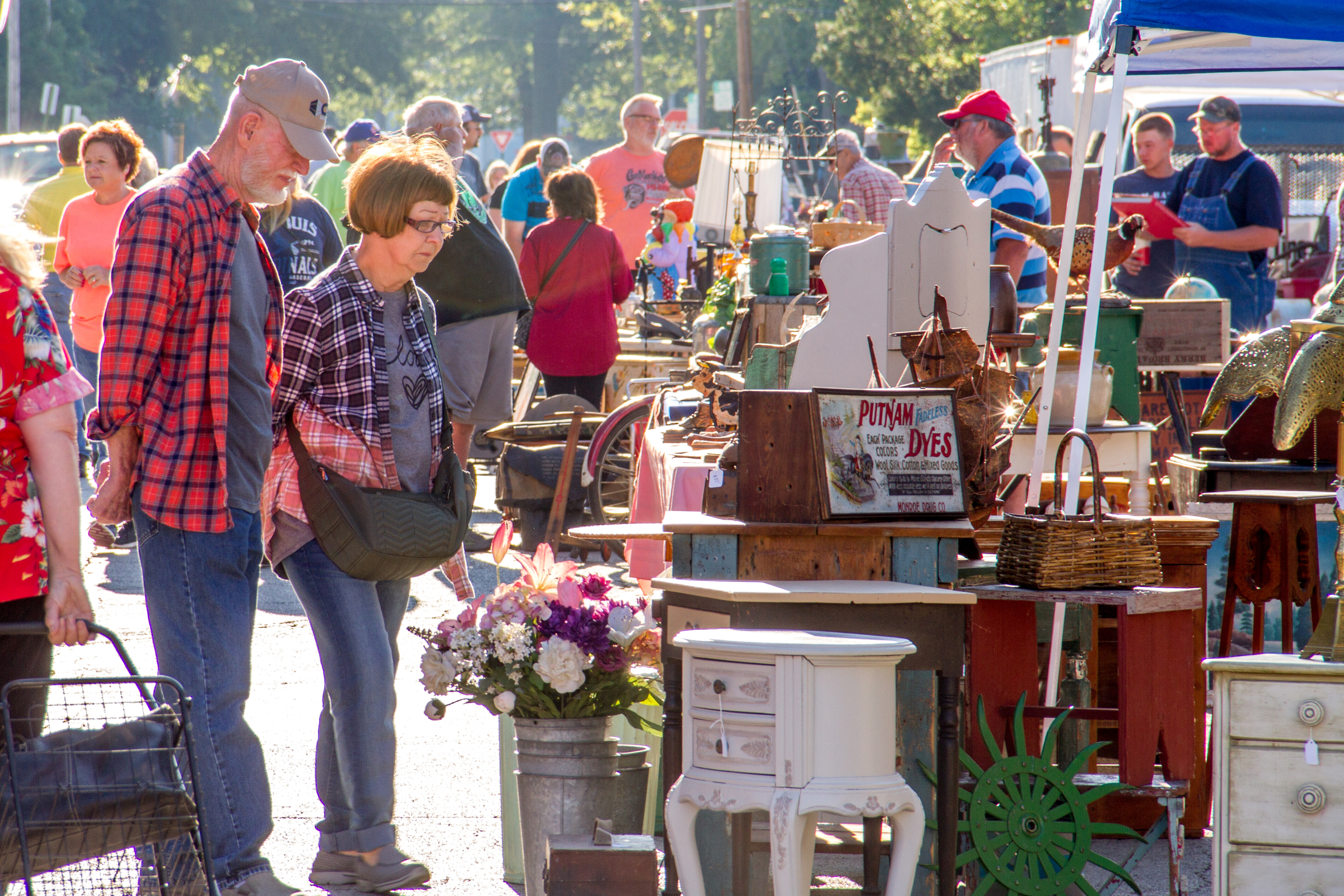 A man and woman looking at a booth at the Litchfield Pickers Market.